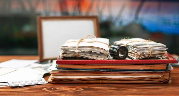 Álbumes con fotos familiares antiguas fotos atadas en una pila sobre una mesa de madera archivo fotográfico de inicio