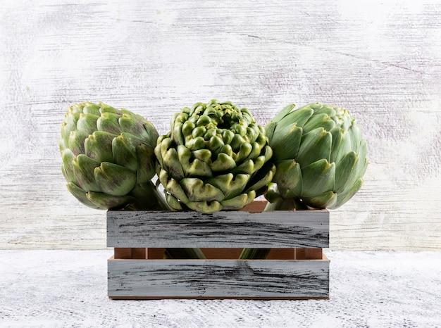 Alcachofa en una caja de madera en un gris claro. vista lateral.