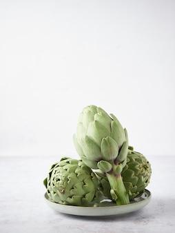 Alcachofas frescas enteras en un plato