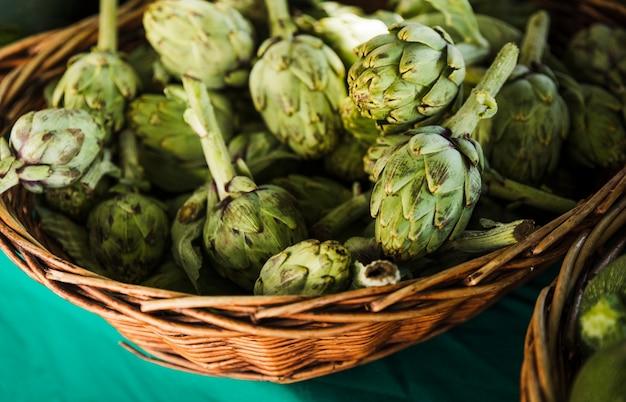 Alcachofas frescas en mimbre en el mercado de agricultores