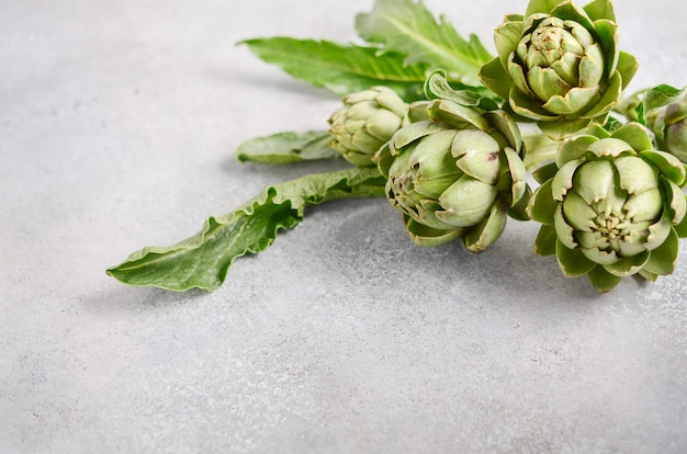 Alcachofas orgánicas frescas sobre un fondo de hormigón gris.