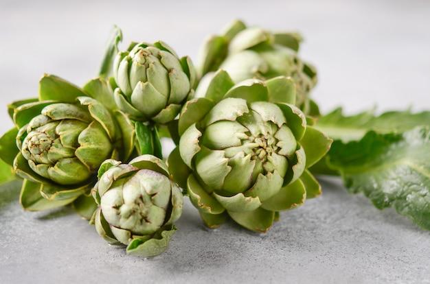Alcachofas orgánicas frescas sobre una mesa de hormigón gris.