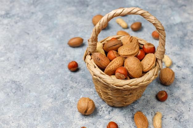 Alcance de la cesta en varios tipos de nueces en cáscaras, cacahuetes, almendras, avellanas y nueces sobre superficie de concreto