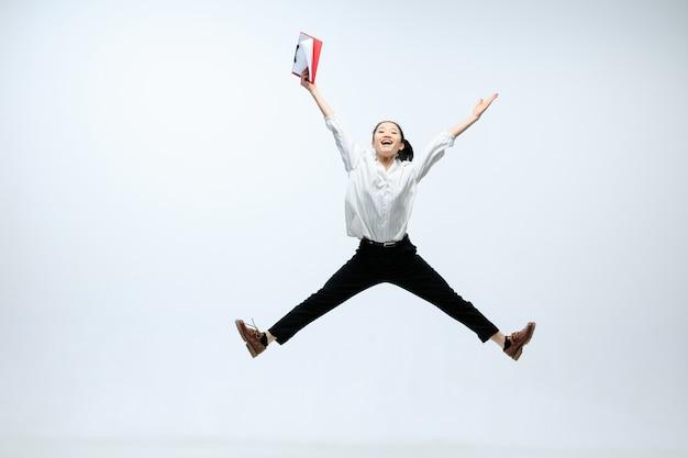 Alcance nuevas alturas para su familia. mujer feliz trabajando en la oficina, saltando y bailando en ropa casual o traje aislado sobre fondo blanco de estudio. negocio, puesta en marcha, concepto de espacio abierto de trabajo.