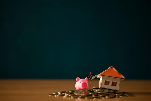 Una alcancía colocada en las monedas de oro apiladas y la casa de la pizarra.