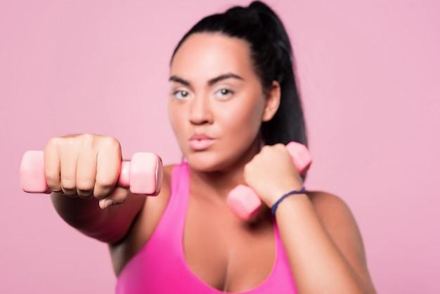 Alcanzando metas. primer plano de mujer gordita con mancuernas y boxeo