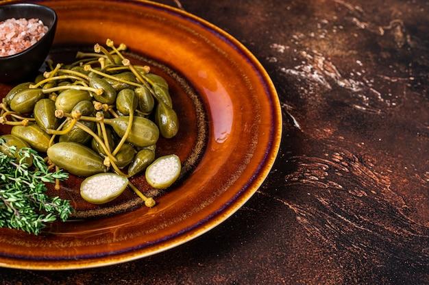 Alcaparras en conserva marinadas en un plato rústico. fondo oscuro. vista superior. copie el espacio.