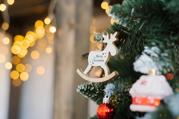 Alce o ciervos de madera del juguete del árbol de navidad en el árbol de navidad con las luces.