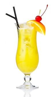 Alcohol amarillo coctel con bayas y rodaja de naranja aislado