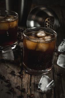 Alcohol. bebidas, boozy black russian cocktail con vodka y licor de café en la mesa de madera rústica. copia espacio