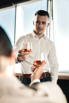 Alcohol con jefe. hombre guapo joven con camisa blanca bebiendo alcohol con su jefe