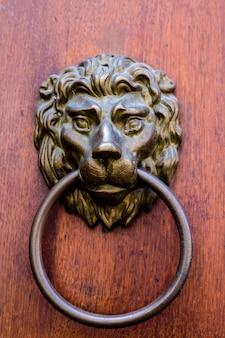 Aldaba de latón antiguo con forma de cabeza de león., elemento de puerta con león metálico