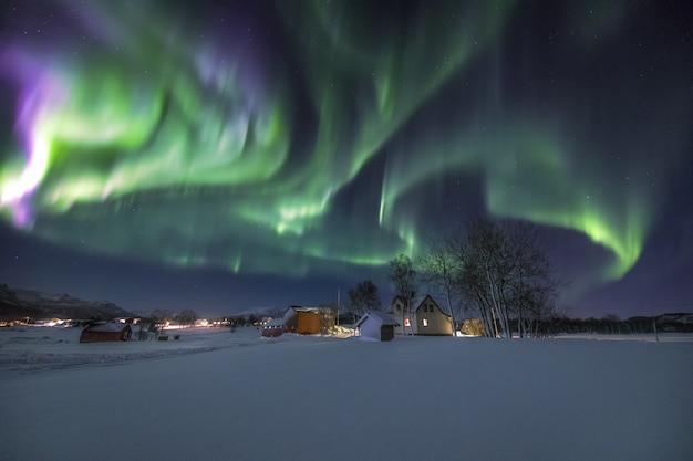 Aldea en el suelo cubierto de nieve bajo la hermosa aurora boreal en el cielo en noruega