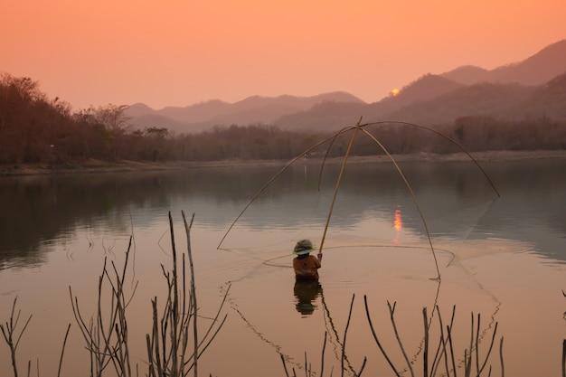 Los aldeanos están atrapando peces por trampa de peces (trampa de red) en el embalse
