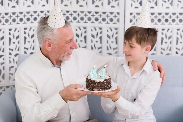 Alegre abuelo y nieto mirándose mientras sostiene un delicioso pastel con una vela