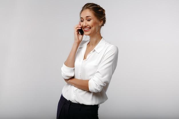 Alegre afable empresaria positiva con un teléfono celular. conversacion. retrato de negocios