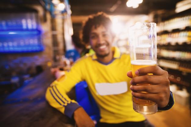 Alegre aficionado al fútbol en jersey saluda a la victoria de su club con una pinta de cerveza.
