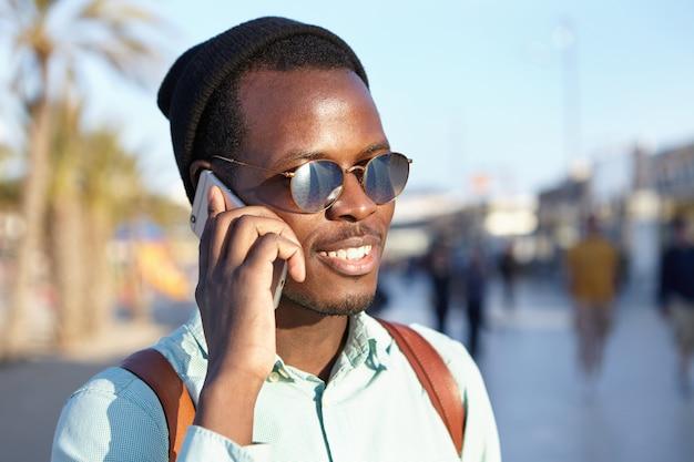 Alegre alegre estudiante afroamericano en gafas de sol redondas y sombreros haciendo llamada telefónica