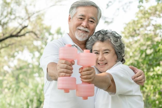 Alegre anciano asiático y senior mujer asiática con mancuernas para hacer ejercicio en el parque, sonriendo con buena salud juntos