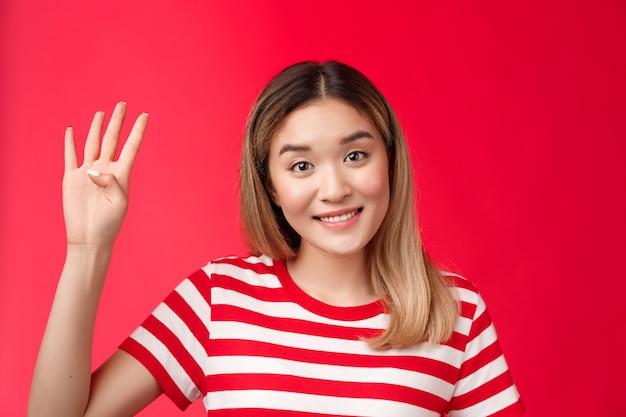 Alegre apuesto linda chica rubia asiática mostrar número cuatro dedos sonriendo encantadora quiere participar ...