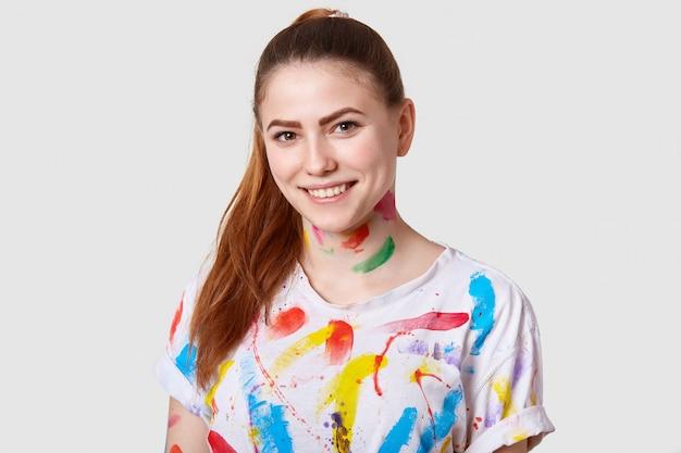 Alegre artista femenina europea contenta tiene cola de caballo, sonrisa de dientes, muestra dientes blancos y parejos, vestida con una camiseta informal
