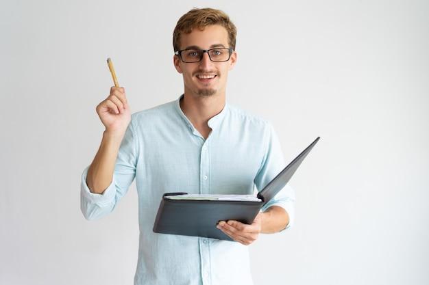 Alegre asesor financiero emprendedor con barba levantando la pluma mientras tiene idea