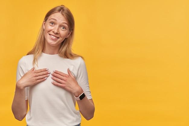Alegre bastante joven rubia con pecas en camiseta blanca se ve feliz y apuntando a sí misma con las manos sobre la pared amarilla mantiene las manos en el pecho