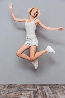 Alegre bastante joven saltando en el aire sobre pared gris