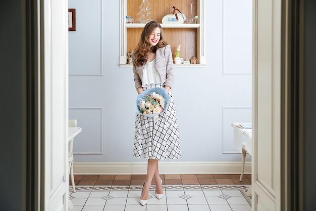 Alegre, bastante, mujer joven, con, largo, pelo rizado, posición, en, café, y, tenencia, ramo de flores