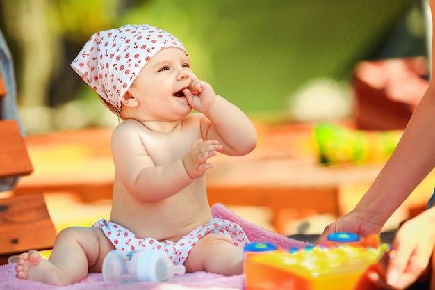 Alegre bebé sentado con juguetes