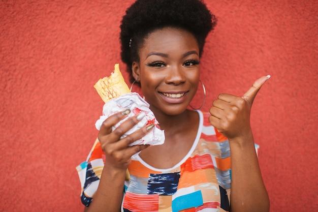 Alegre chica afroamericana con hamburguesa en la mano muestra el pulgar hacia arriba gesto sobre la pared roja