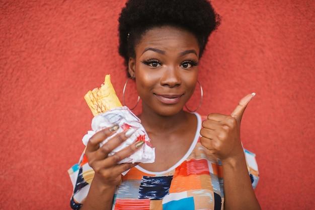 Alegre chica afroamericana con hamburguesa en la mano muestra el pulgar hacia arriba gesto