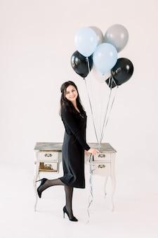 Alegre chica caucásica positiva en vestido negro tiene manojo de globos de aire, de pie cerca de la mesa blanca vintage con cajones, espera invitados, aislado sobre fondo blanco. concepto de fiesta de cumpleaños