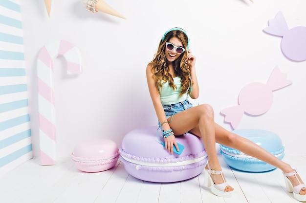 Alegre chica delgada con piernas largas sentada en un gran macarrón morado y riendo. retrato interior de una mujer joven y bonita en zapatos blancos descansando en su habitación y escuchando música en auriculares.