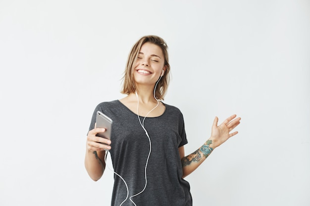 Alegre chica guapa joven sonriente escuchando música en auriculares bailando. ojos cerrados.