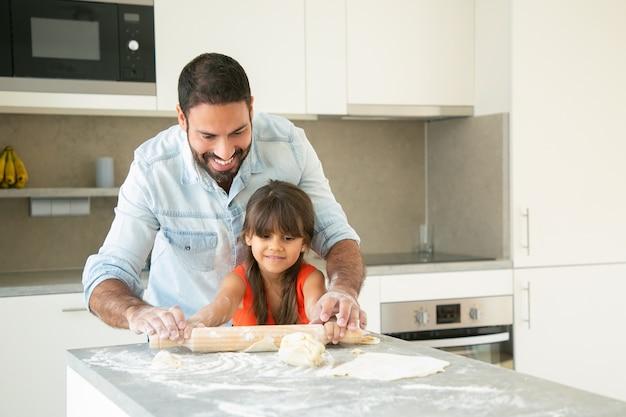 Alegre chica latina y su papá rodando y amasando masa en la mesa de la cocina con harina en polvo.