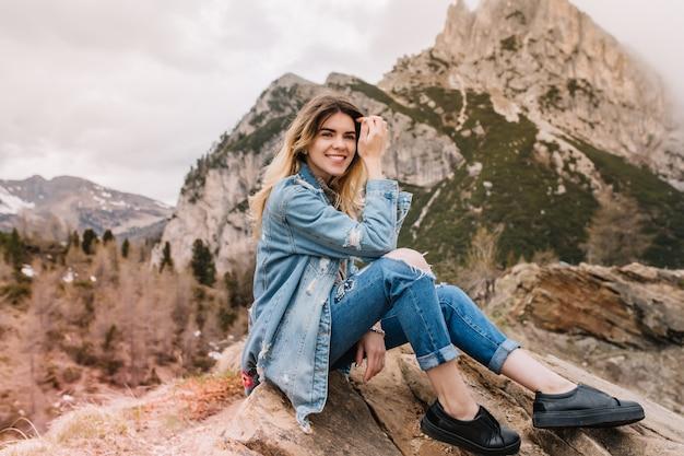 Alegre chica rubia descansa sobre piedra después de escalar las montañas y reír