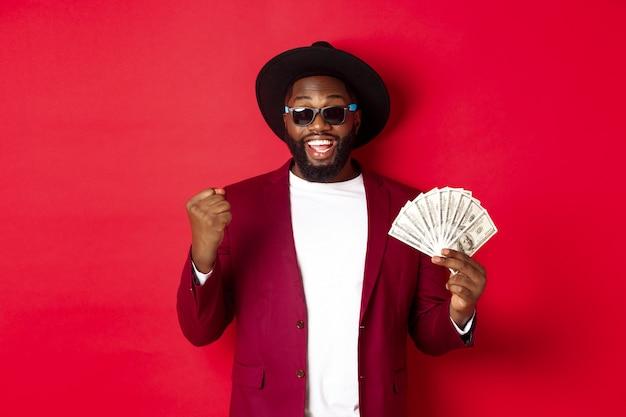 Alegre chico afroamericano con gafas de sol, sombrero negro y chaqueta, ganando premios en efectivo, sosteniendo dólares y luciendo satisfecho, de pie sobre fondo rojo.