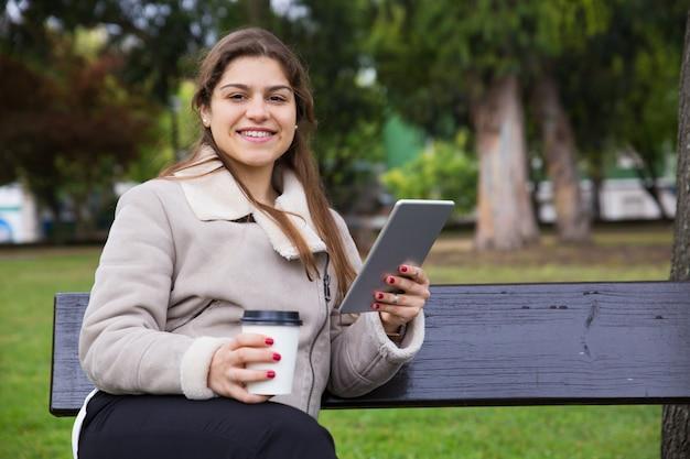Alegre colegiala latina con tableta tomando café para llevar