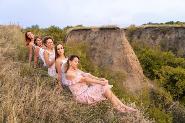 Una alegre compañía de hermosas amigas disfruta de un pintoresco panorama de las verdes colinas al atardecer
