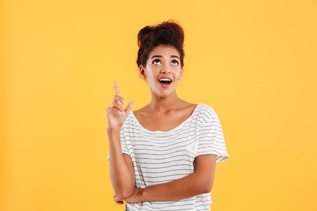 Alegre dama afroamericana apuntando con el dedo hacia arriba para copiar espacio