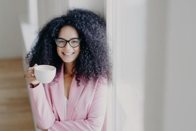 Alegre dama afroamericana de pelo rizado tiene descanso para tomar café, sostiene una taza de bebida blanca