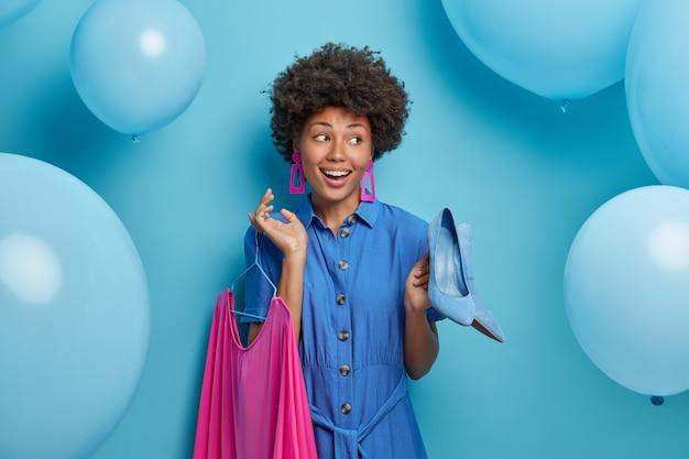 Alegre dama afroamericana positiva elige fuera para la cita, sostiene zapatos azules de tacón alto y vestido rosado en perchas, se prepara para la fiesta y celebración, posa sobre una pared azul con globos inflados
