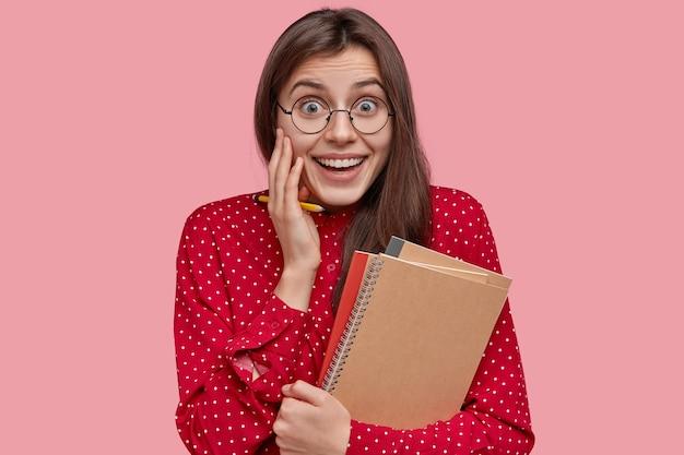 Alegre dama alegre con una gran sonrisa, tiene dientes blancos, sostiene blocs de notas, lápiz, hace registros en el organizador, feliz de ser promovida en el trabajo