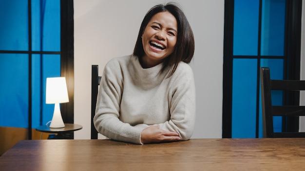 Alegre dama de asia de mediana edad que se siente feliz, sonríe y mira a la cámara usando el teléfono para hacer una videollamada en vivo en la sala de estar en casa por la noche.