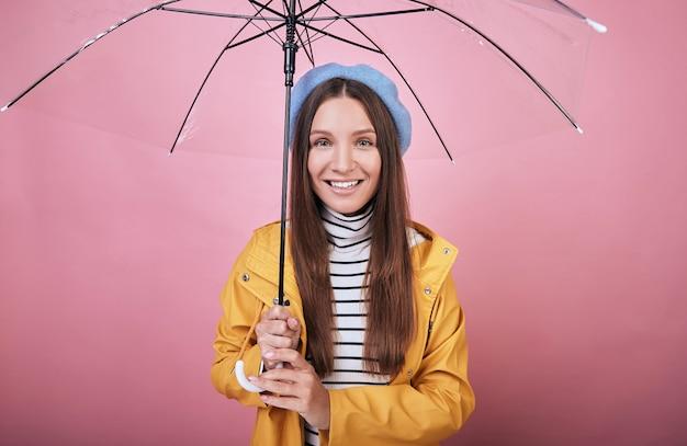 Alegre dama de boina azul, blusa a rayas y chubasquero con paraguas