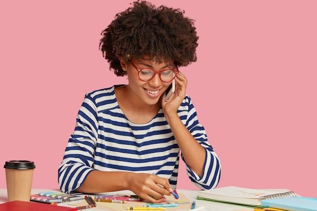 Alegre dama negra disfruta de pintar, hace un cuadro en una hoja de papel en blanco, usa lentes ópticos, tiene una conversación telefónica, sonríe suavemente mientras habla de algo agradable, aislado en una pared rosa