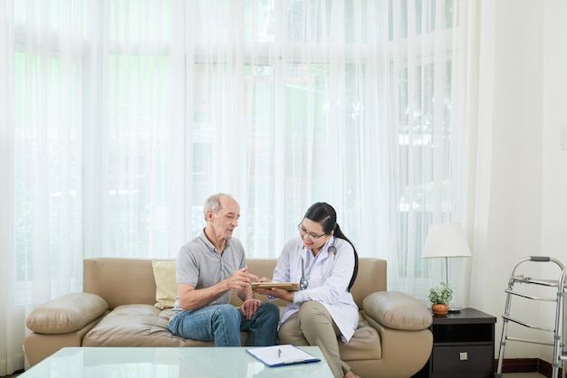 Alegre doctora asiática visitando pacientes varones caucásicos senior en casa