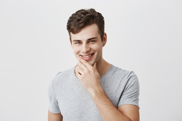 Alegre, elegante, guapo hombre caucásico con camiseta gris, mantiene la mano debajo de la barbilla, sonríe suavemente, feliz o contento de escuchar cumplidos, se siente orgulloso de sí mismo, tiene una expresión positiva