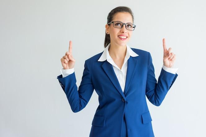 Alegre emprendedora joven empresaria apuntando hacia arriba.